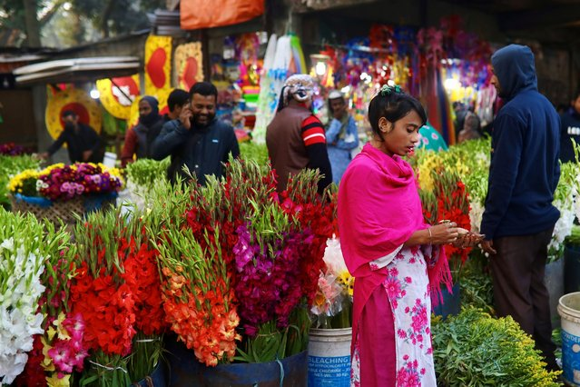 A woman counts money after selling flowers at a flower market in Dhaka, Bangladesh, December 23, 2020. (Photo by Mohammad Ponir Hossain/Reuters)