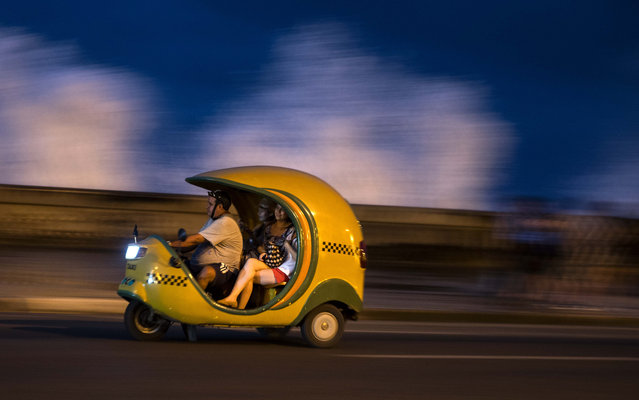 "Tourists travel in a ""Coco taxi"" along the Malecon as waves break above the sea wall in Havana, Cuba, Saturday, December 5, 2015. Coco taxis are one of many kinds of taxis in the capital fashioned out of motorcycles, popular with both tourists and locals. (Photo by Ramon Espinosa/AP Photo)"