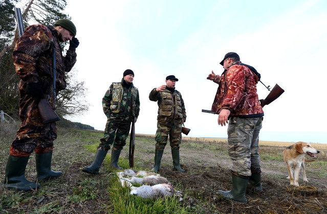 Hunters talk after a hunt in a field near the village of Novosyolki, Belarus November 5, 2016. (Photo by Vasily Fedosenko/Reuters)