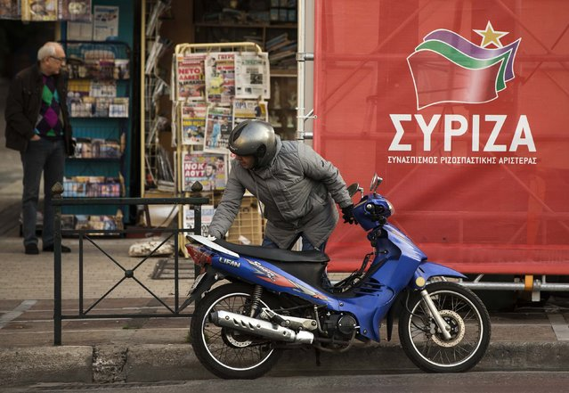 A man pushes his motorbike near a banner of opposition radical leftist Syriza party in Athens January 21, 2015. The parliamentary elections will take place on Sunday. (Photo by Marko Djurica/Reuters)