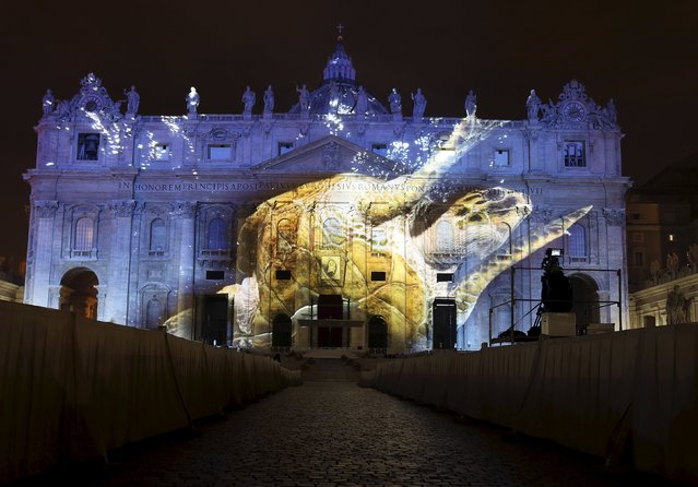"""A picture of a turtle by David Doubilet, part of an art projection featuring images of humanity and climate change artistically rendered by Obscura Digital, is projected onto the facade of St. Peter's Basilica, as part of an installation entitled """"Fiat Lux: Illuminating our Common Home"""" as a gift to Pope Francis on the opening day of the Extraordinary Jubilee, at the Vatican, December 8, 2015. (Photo by Stefano Rellandini/Reuters)"""