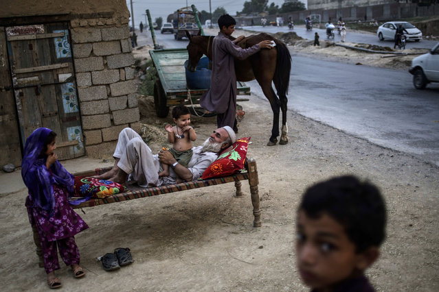 Pakistani Abdulrahman Qassim, 62, lies on a bed outside his home playing with his one-year-old grandson Abdulaziz, and his granddaughter Zulikha, 6, left, on the outskirts of Islamabad, Pakistan, Monday, June 24, 2013.  Abdulrahman and his family fled their home from Pakistan's tribal region of Mohmand Agency, due to fighting between the Taliban and the army, and took refuge in Islamabad. (Photo by Muhammed Muheisen/AP Photo)