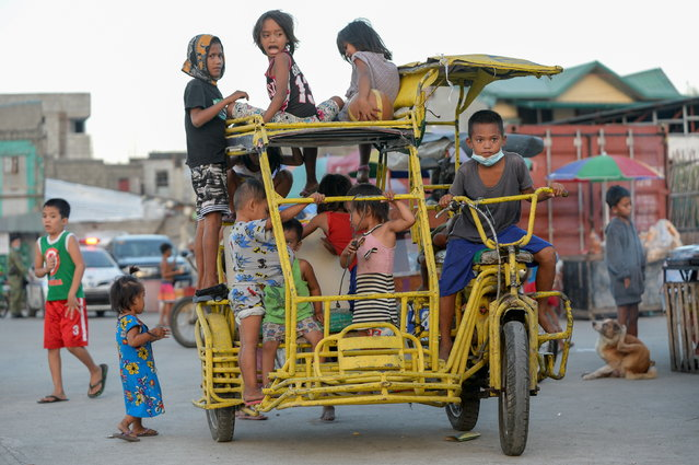 Children ride on a pedicab at a park in Baseco compound, Manila, Philippines, December 16, 2020. (Photo by Lisa Marie David/Reuters)