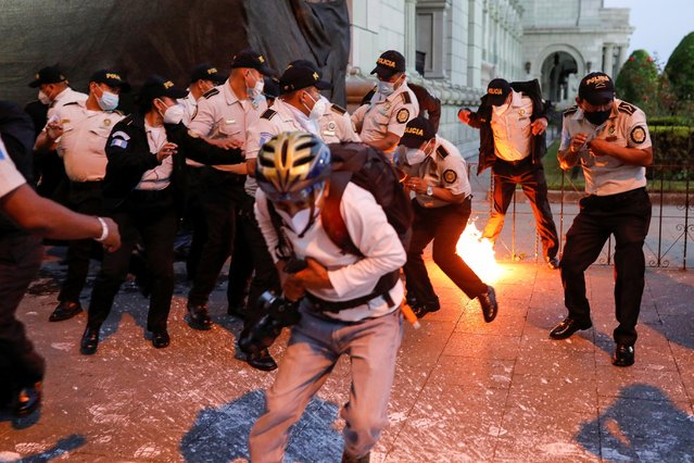 Police officers react as a molotov cocktail from demonstrators falls during a protest to demand the resignation of Guatemala's President Alejandro Giammattei in Guatemala City, Guatemala on November 28, 2020. (Photo by Luis Echeverria/Reuters)
