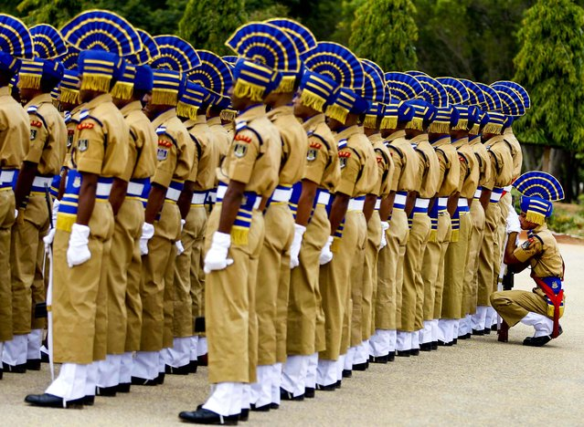 An Indian Central Reserve Police Force soldier takes a break as he sits behind his fellow soldiers during a parade ceremony of 945 recruits in Bangalore, India, on July 9, 2013. CRPF is one of the largest paramilitary forces in the world with a strength of over 250,000 personnel, meant to maintain law and order and contain insurgency across India and are also deployed for United Nations missions. (Photo by Aijaz Rahi/Associated Press)