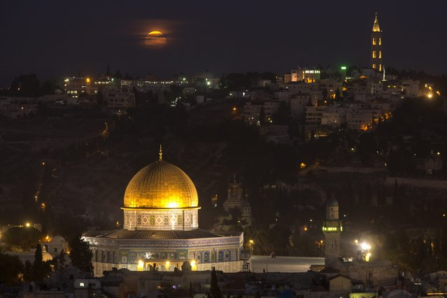 The Super Moon rises above the Old city of Jerusalem with its distinctive golden Dome of the Rock on the Hareem el-Sharif (The Noble Sanctuary), or the Temple Mount, in Jerusalem, Israel, 14 November 2016. Behind is the Arab neighborhood of The Mount of Olives and the Russian Church in A-Tur. (Photo by Jim Hollander/EPA)