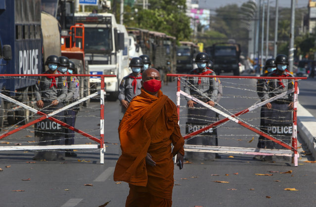 A Buddhist monk walks along a road as police stand watch in Mandalay, Myanmar, Wednesday, February 24, 2021. (Photo by AP Photo/Stringer)