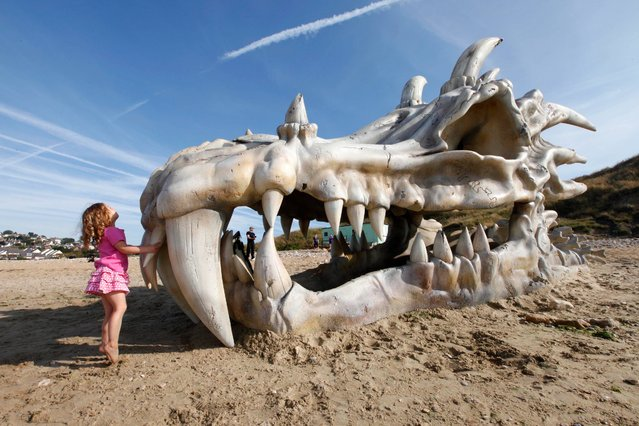 """Pantha Bradbury, three, stands in front of a 39 feet-wide dragon skull, which has been created to celebrate the launch of HBO's """"Game of Thrones"""" Season 3 on the television and movie service, blinkbox, on Charmouth beach on the Jurassic coast in Lyme Regis, Dorset, on July 15, 2013. (Photo by David Parry/PA Wire)"""