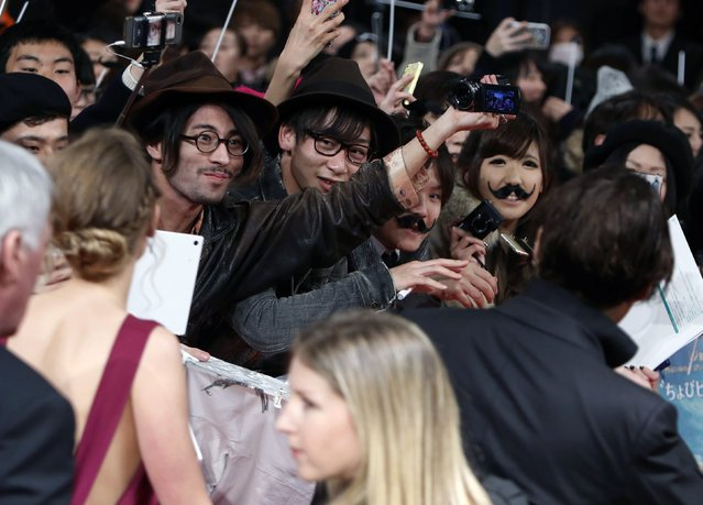"""A fan of actor Johnny Depp records video as Depp (R) and actress Amber Heard (2nd L) walk on the red carpet during the Japan premiere of """"Mortdecai"""" in Tokyo January 27, 2015. (Photo by Yuya Shino/Reuters)"""