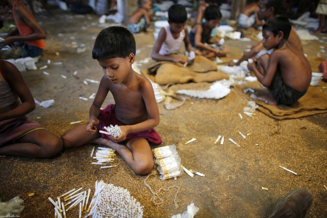 """Children fill up empty cigarettes manually with locally grown tobacco in a small bidi (cigarette) factory at Haragach in Rangpur district, Bangladesh July 11, 2013. According to a 2012 study by US-based NGO, Campaign for Tobacco-Free Kids, over 45,000 people in Bangladesh are employed in manufacturing inexpensive cigarettes known as bidis and this number includes """"many women and children working in household based establishments where they make low wages and live in poverty."""" A 2011 research paper about bidi workers in Bangladesh, published in the journal Tobacco Control, says that working conditions can involve poor ventilation and exposure to tobacco dust, which can cause a range of health problems including respiratory and skin diseases. International attention has been focused on workers' safety in Bangladesh since the disaster at Rana Plaza, a garment factory complex which collapsed in April, killing 1,132 workers. (Photo by Andrew Biraj/Reuters)"""