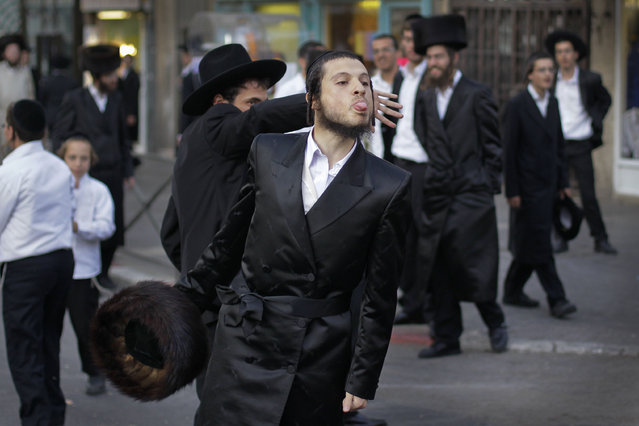 An Ultra-Orthodox Jew makes a derogatory gesture to media and police, due to them working on a Saturday covering and policing the protest, at a demonstration against a municipal parking lot that is open on the Jewish Sabbath, in Jerusalem Saturday, July 16, 2011. (Photo by Ben Curtis/AP Photo)