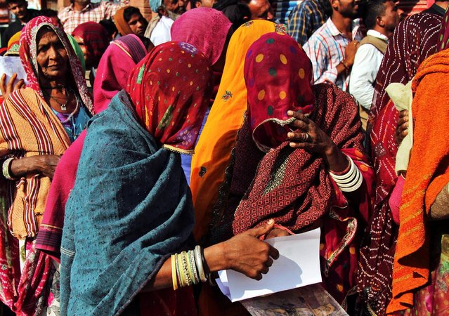 Women check their documents as they queue outside a bank to exchange and deposit their old high denomination banknotes in Gagwana village in the desert Indian state of Rajasthan, India, November 16, 2016. (Photo by Himanshu Sharma/Reuters)