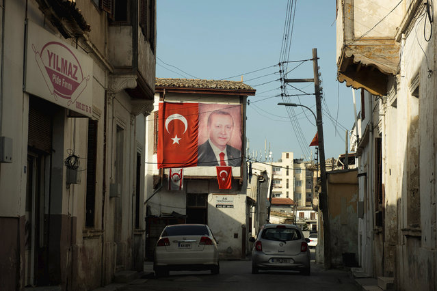 A portrait of Turkish President Recep Tayip Erdogan and Turkish flags are seen on a building in the Turkish occupied area at the Turkish Cypriot breakaway north part of divided capital Nicosia, Cyprus, Wednesday, March 10, 2021. A group representing Greek Cypriot and Turkish Cypriot left-wing peace organizations on Friday, March 12, condemned the arrest of four Turkish Cypriot activists for allegedly damaging signs in breakaway northern Cyprus professing adoration for Turkish President Recep Tayip Erdogan. (Photo by Nedim Enginsoy/AP Photo)