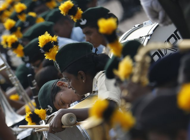 A girl sleeps on her drum before a rehearsal for Sri Lanka's 67th Independence Day celebrations in Colombo February 2, 2015Dinuka Liyanawatte