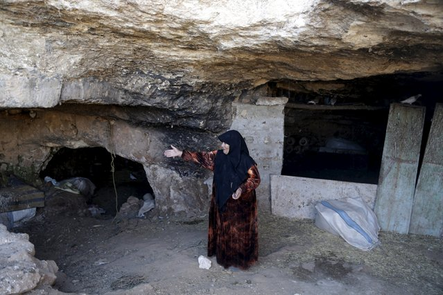 An internally displaced Syrian woman gestures inside her makeshift shelter that is an underground cave in Om al-Seer, southern Idlib countryside, Syria December 26, 2015. (Photo by Khalil Ashawi/Reuters)