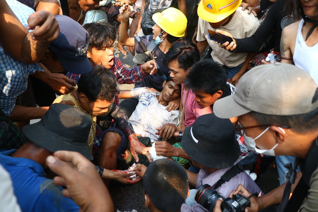 Anti-coup protesters surround an injured man in Hlaing Thar Yartownship in Yangon, Myanmar Sunday, March 14, 2021. A number of people were shot dead during protests in Myanmar's largest city on Sunday, as security forces continued their violent crackdown against dissent following last month's military coup. (Photo by AP Photo/Stringer)