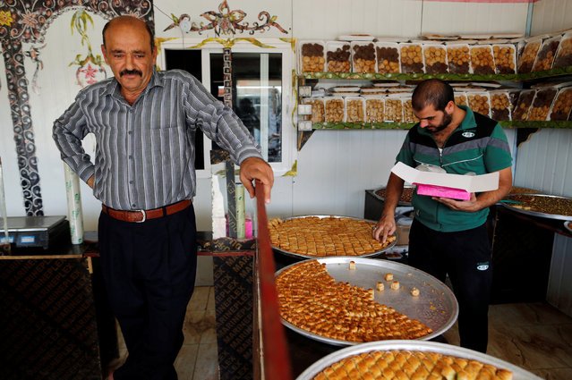 A Syrian refugee (L) sells sweets at his shop in Zaatari refugee camp near the border with Syria, in Mafraq, Jordan October 16, 2016. (Photo by Ammar Awad/Reuters)