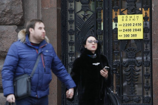People walk past a board showing the currency exchange rate in central Kiev February 6, 2015. A move by Ukraine's central bank to ditch an unofficial peg for the hryvnia has plunged the foreign exchange market into confusion, with buyers of hard currency putting off purchases and sellers holding out for higher levels. (Photo by Valentyn Ogirenko/Reuters)