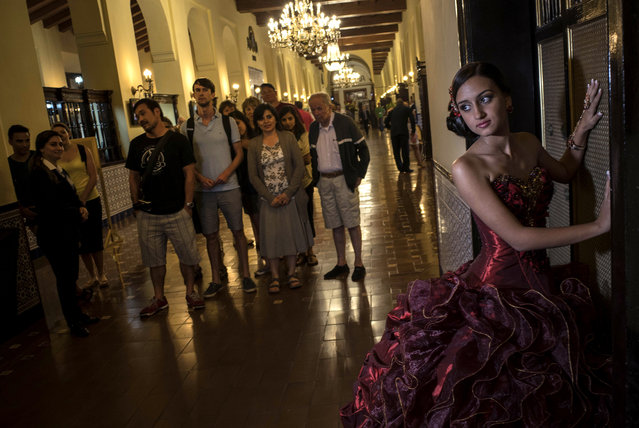 "In this December 3, 2015 photo, Gladys Barroso Quintana, 15, who lives in Cuba, poses for her quinceanera portraits at the National Hotel as tourists watch in Havana, Cuba. Celebrations known as ""quinceaneras"", marking a girl's 15th birthday and recognizing her transition to womanhood, date back centuries in Latin America. Some vestiges of the older celebrations remain, with Latin American girls performing traditional waltzes. But in Cuba, photographs are the main focus. (Photo by Ramon Espinosa/AP Photo)"