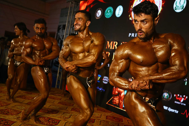 Bodybuilders pose during a body building competition in Karachi, Pakistan, 23 March 2021. The event was organized by the Karachi Body Building Association. (Photo by Shahzaib Akber/EPA/EFE)