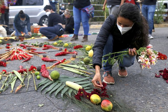 Berta Zuniga, a daughter of environmental and Indigenous rights activist Berta Caceres, places flower petal on an offering at a spiritual ceremony, a day before a trial against one of the alleged masterminds of the killing of Caceres, in Tegucigalpa, Honduras, Monday, April 5, 2021. The trial of Roberto David Castillo is expected to run through April. The government has already convicted seven people in Caceres' murder, but is Castillo is considered a potentially critical link to those who ordered it. (Photo by Elmer Martinez/AP Photo)