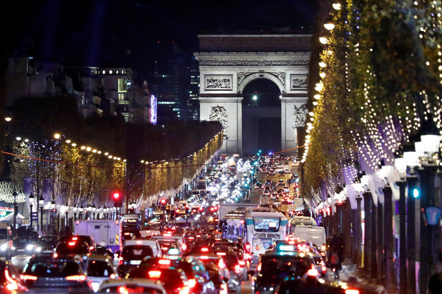 Christmas holiday lights hang from trees to illuminate the Champs Elysees avenue in Paris as rush hour traffic fills the avenue leading up to the Arc de Triomphe, France, November 21, 2016. (Photo by Charles Platiau/Reuters)