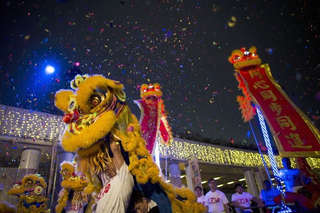 Lion dance troupes perform during a Chinese New Year evening parade at Hong Kong's Tsim Sha Tsui shopping district February 19, 2015. (Photo by Tyrone Siu/Reuters)