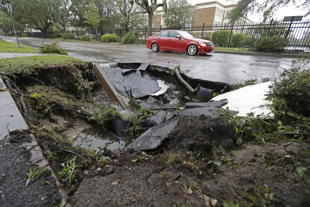 A car travels past a sinkhole in downtown Wilmington, N.C., after Hurricane Florence traveled through the area Sunday, September 16, 2018. (Photo by Chuck Burton/AP Photo)