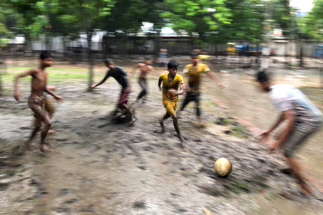 Boys play football on muddy ground of a park during rain in Dhaka, Bangladesh, July 24, 2018. (Photo by Mohammad Ponir Hossain/Reuters)