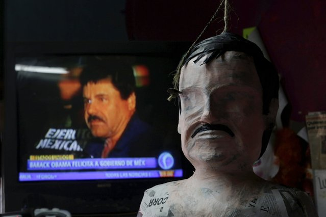 """A pinata in progress depicting the drug lord Joaquin """"El Chapo"""" Guzman is seen in front of a television showing a news bulletin of him, at a workshop in Reynosa, in Tamaulipas state, Mexico, January 13, 2016. (Photo by Daniel Becerril/Reuters)"""