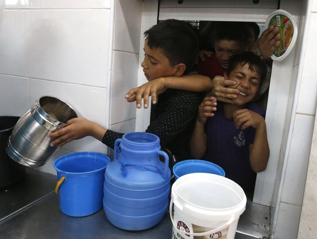 Palestinian children jostle one another outside a charity kitchen run by the Islamic Waqf in the West Bank town of Hebron, to receive free food on May 20, 2018, during the holy Muslim month of Ramadan. (Photo by Hazem Bader/AFP Photo)