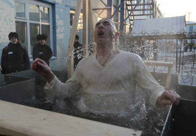 An inmate immerses himself in water at high-security penal colony number 6 on the eve of the Orthodox Epiphany, with the air temperature at about minus 29 degrees Celsius (minus 20.2 degrees Fahrenheit), in the Siberian city of Omsk, Russia, January 18, 2016. (Photo by Dmitry Feoktistov/Reuters)