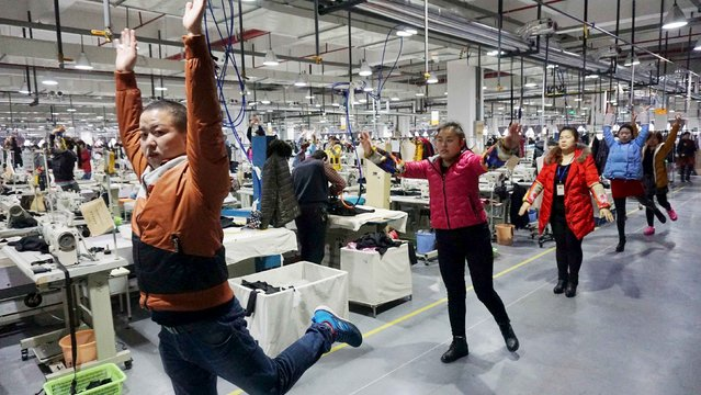 Employees stretch as they practice a routine exercise during a break at a garment factory in Jiaxing, Zhejiang Province, China, January 12, 2016. The factory organizes exercises for over 1,200 employees twice a day, during their break at 9:30a.m and 2:30p.m, for their well-being, local media reported. (Photo by Reuters/Stringer)