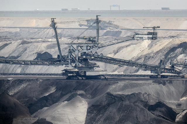 Giant bucket-wheel excavators extract coal at the controversial Garzweiler surface coal mine near Jackerath, west Germany, Thursday, April 29, 2021. Germany's top court ruled Thursday that the country's government has to set clear goals for reducing greenhouse gas emissions after 2030, arguing that current legislation doesn't go far enough in ensuring that climate change is limited to acceptable levels. (Photo by Martin Meissner/AP Photo)