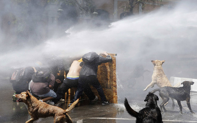 Demonstrators are hit by a jet of water as they clash with riot police during a protest to demand changes to the public education system in Santiago, Chile, on Oktober 17, 2013. (Photo by Ivan Alvarado/Reuters)