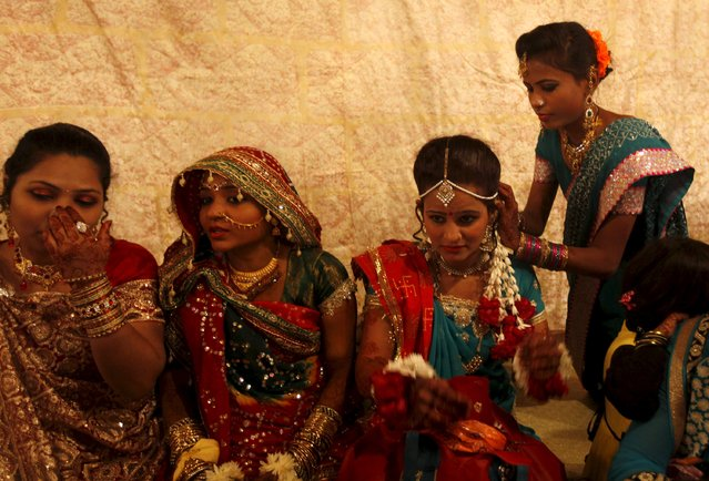 A bride and her party prepare as they wait for their wedding to start during a mass marriage ceremony in Karachi, Pakistan, January 24, 2016. The Pakistan Hindu Council organized a mass marriage ceremony where a total of 60 couples from the Hindu community residing in Pakistan's Sindh province took wedding vows, according to the council. (Photo by Akhtar Soomro/Reuters)