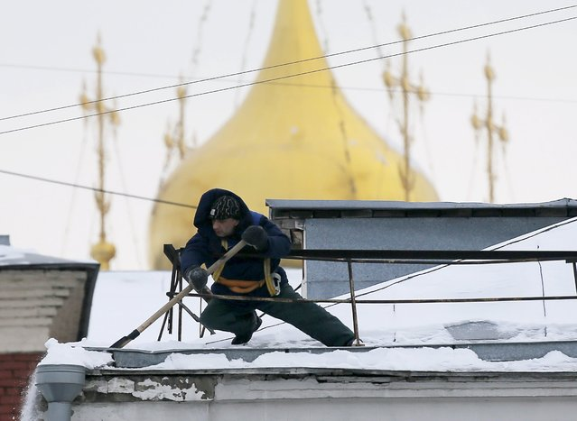 A worker removes snow from the roof of a building in Moscow, Russia, January 25, 2016. (Photo by Maxim Shemetov/Reuters)