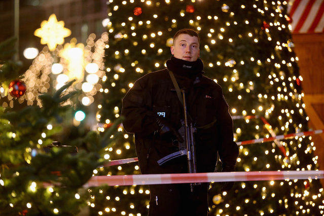 A policeman with a submachine gun stands at the area after a lorry truck ploughed through a Christmas market on December 19, 2016 in Berlin, Germany. Several people have died while dozens have been injured as police investigate the attack at a market outside the Kaiser Wilhelm Memorial Church on the Kurfuerstendamm and whether it is linked to a terrorist plot. (Photo by Sean Gallup/Getty Images)