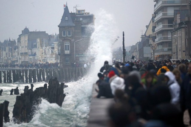 """People stand along the waterfront as a wave crashes onto a seawall durng the rising tide in Saint Malo, March 21, 2015. Parts of the French coast will be on alert for the so-called """"tide of the century"""", with tidal coefficients of 118 and 119 respectively on March 20 and 21. (Photo by Stephane Mahe/Reuters)"""