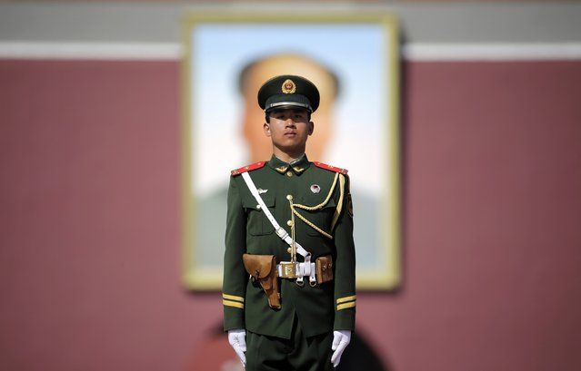 A paramilitary police officer stands guard in front of a giant portrait of China's late Chairman Mao Zedong during the closing session of the Chinese People's Political Consultative Conference (CPPCC), on Beijing's Tiananmen Square, March 13, 2015. (Photo by Jason Lee/Reuters)