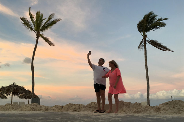 BAHAMAS: A couple videochats on their smartphone on the beach in the aftermath of Hurricane Matthew near Nassau, Bahamas October 9, 2016. (Photo by Carlo Allegri/Reuters)