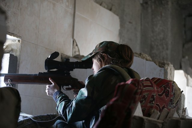 A female Syrian sniper from the Republican Guard commando battalion aims fire during clashes with rebels in the restive Jobar area, in eastern Damascus, on March 25, 2015. (Photo by Joseph Eid/AFP Photo)