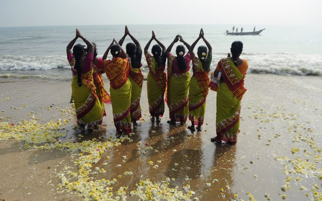 Indian women offer prayers during a ceremony for the victims of the 2004 tsunami at Marina Beach in Chennai on December 26, 2016. (Photo by Arun Sankar/AFP Photo)
