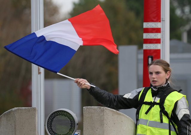 A demonstrator holds a french flag at the toll gates on a motorway at Biarritz southwestern France, Wednesday, December 5, 2018.T he concessions made by French president Emmanuel Macron's government in a bid to stop the huge and violent anti-government demonstrations seemed on Wednesday to have failed to convince protesters, with trade unions and disgruntled farmers now threatening to join the fray. (Photo by Bob Edme/AP Photo)