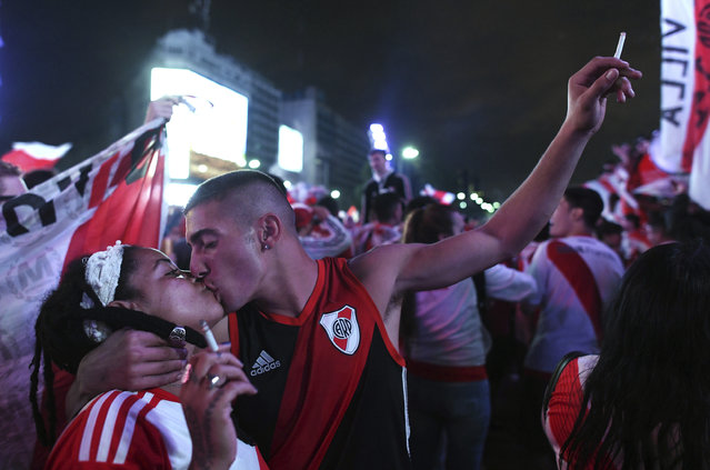 River Plate soccer fans kiss as they celebrate their team's 3-1 victory over Boca Juniors and clenching the Copa Libertadores championship title, at the Obelisk in Buenos Aires, Argentina, Sunday, December 9, 2018. The South American decider was transferred from Buenos Aires to Madrid, Spain after River fans attacked Boca's bus on Nov. 10 ahead of the second leg. (Photo by Gustavo Garello/AP Photo)