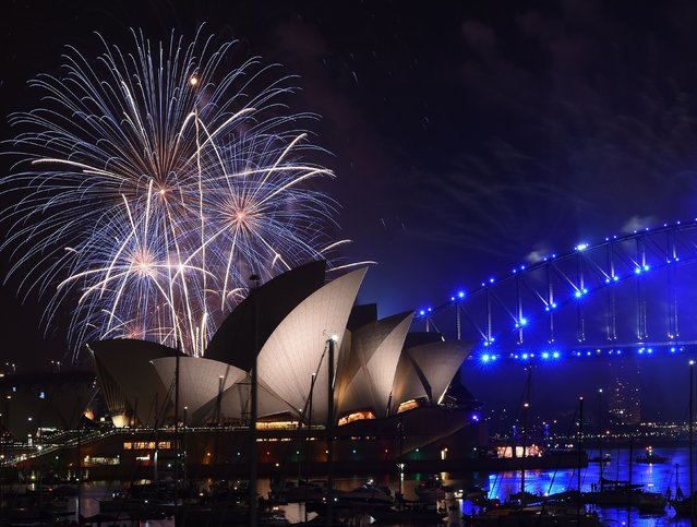 New Year fireworks illuminate the sky over the iconic Opera House and Harbour Bridge in Sydney on January 1, 2017. (Photo by Saeed Khan/AFP Photo)