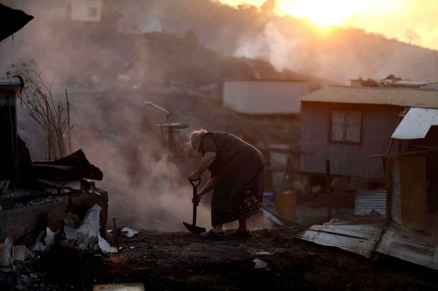 Nora Villarroel, 59, tries to put out the fire in the remains of her burned house in Valparaiso, Chile, Monday, January 2, 2017. The fire, driven by strong winds, swept through forest land in the hills outside the Chilean port of Valparaiso, destroying dozens of homes and sending a pall of heavy smoke down onto the city. (Photo by Luis Hidalgo/AP Photo)