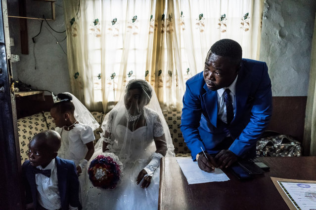 Chinyere (Godgiven) and her husband-to-be Jones (R) prepare wedding documents during a service at the Evangelic Calvary Life Mission Church on May 28, 2017 in the Osusu district of Aba. (Photo by Marco Longari/AFP Photo)