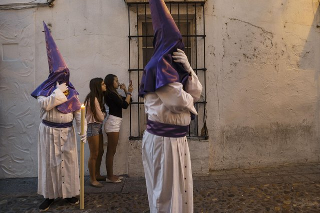"""Penitents take part in """"Santisimo Cristo del Perdon, Maria Santisima de la Piedad y San Juan Evangelista"""" Holy Week procession while girls take snapshots in Arcos de La Frontera, Spain, Wednesday, April 1, 2015. Hundreds of processions take place throughout Spain during the Easter Holy Week. (Photo by Daniel Ochoa de Olza/AP Photo)"""