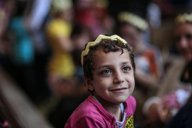 An Egyptian Orthodox Christian boy celebrates Palm Sunday during a service in the Samaan el-Kharaz Church in the Mokattam district of Cairo, Egypt, Sunday, April 5, 2015. (Photo by Mosa'ab Elshamy/AP Photo)